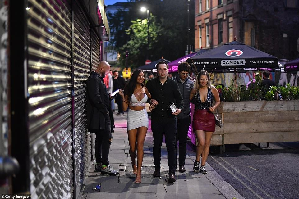 30403212-8490751-MANCHESTER_Two_couples_walk_past_bars_on_Thomas_Street_in_the_No-a-148_1593930321904.jpg